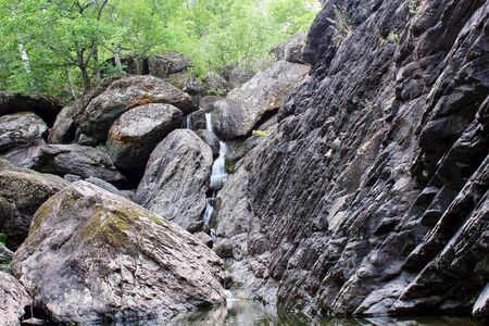 Mountain waterfall. Mountain river among gray huge boulders in the middle of a dense forest