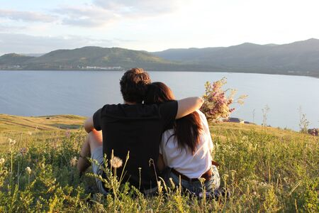 Loving couple on top of the mountain. Embrace. Sunset. A young girl with long hair and her boyfriend. Love. Man and woman.
