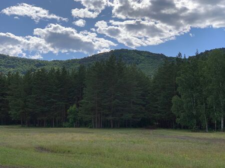 Panoramic view. Beautiful summer landscape. Mountains, blue sky and green fields, forestA group of clouds in the sky 스톡 콘텐츠