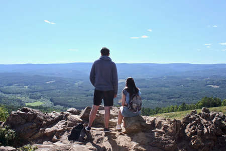 A guy and a girl standing on top of a mountain, admiring the panoramic top view of the mountains, hills, sky