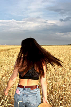 Young happy beautiful slender girl with long hair and a hat in a wheat field. Summer landscape