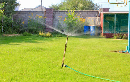 Automatic lawn sprinkler watering green grass. Sprinkler with automatic system. Garden irrigation system watering lawn