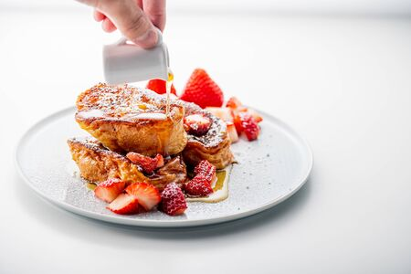 French toast with fresh strawberries and honey syrup on white plate. Delicious dessert image. Stock Photo