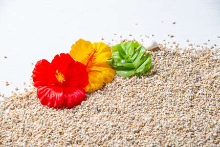 Artificial hibiscus flowers on sand.
