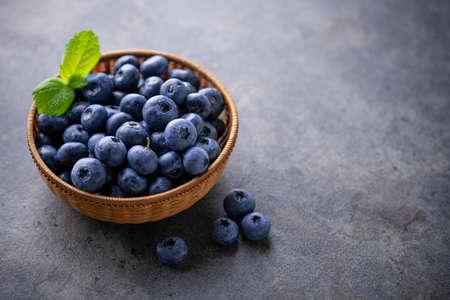 Fresh ripe blueberries in basket on dark background.