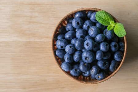 Fresh ripe blueberries in basket on wooden background.