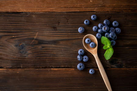 Fresh ripe blueberries in spoon on wooden background.