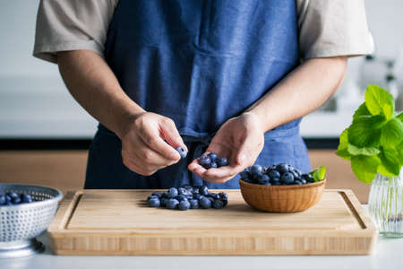 Man pick fresh ripe blueberries.
