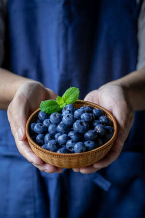 Man holds a wicker basket of blueberries.