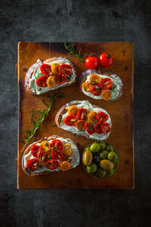 Sliced bread with cream cheese and homemade dried tomatoes on wooden board.Delicious snack. 写真素材