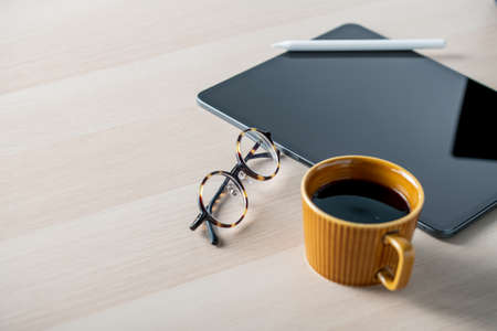 Digital tablet on table with stylus pen,cup of coffee,eyeglasses. Technology lifestyle image. 写真素材