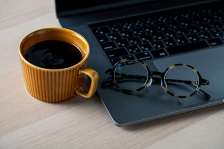 Laptop computer on wooden table. with cup of coffee and eyeglasses. technology lifestyle image. 写真素材