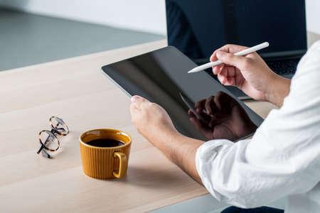 Man using stylus pen for digital tablet.