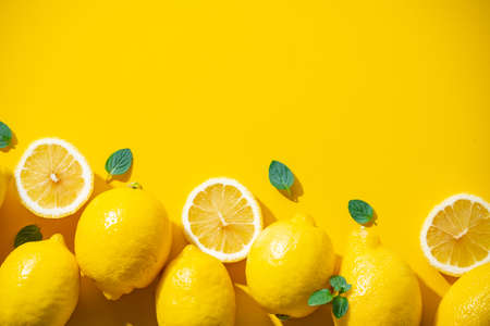 Lemons on yellow background. Flesh lemons on yellow text space.