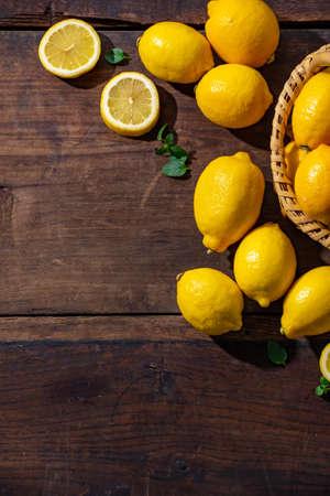 Lemons on wooden background. Flesh lemons on wooden text space.