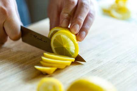 Man cutting lemons in kitchen.
