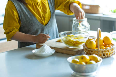 Woman making lemonade in kitchen. Archivio Fotografico