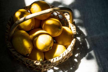 Ripe lemons in basket at sunlight. Archivio Fotografico