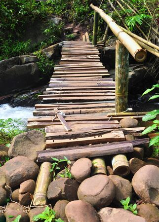 Old wooden bridge across the stream in the forest, Phu Soi Dao National Park, Thailand.
