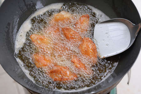 Chicken wings are frying in an iron pan