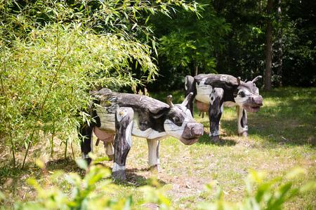 reckon: wooden milk cow figures on sunny meadow grassland