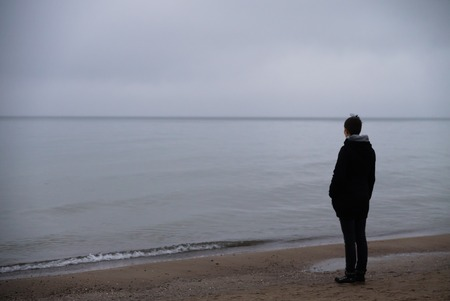 longing: woman on the beach longing looking to the foggy misty sea