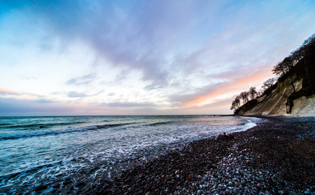 wideangle: ultra wideangle sea landscape with stone beach and lilac purple evening atmosphere Stock Photo