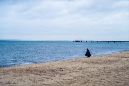 mujer mirando el horizonte: una mujer solitaria buscando tristemente sobre el borde de mar y los acantilados en el condado