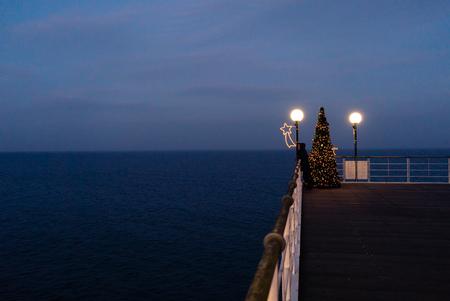 Beautiful christmas scenery panorama pier architecture on sea-bridge with decorated Xmas Tree in Christmas, Baltic Sea Germany Reklamní fotografie