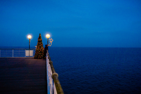 lucid: christmas tree on bridge at sea in blue hour evening Stock Photo