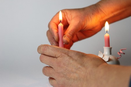 lit candle: woman female hand Holding a lit candle