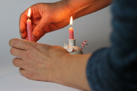 reverent: Candle in female hands on light background