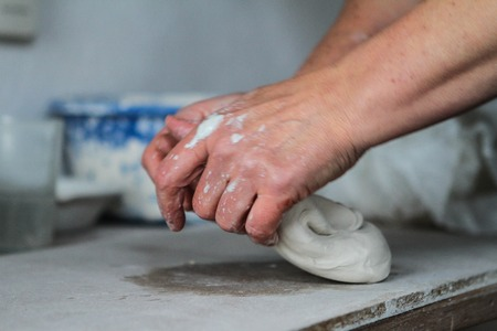 fireclay: Adult female potter master preparing the clay on table. Front view, closeup, hands only, unrecognizable. Art and business, hobby and freelance working concept.