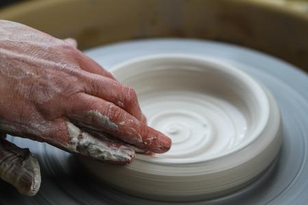 potters wheel: Potter works. Crockery creation process in pottery on potters wheel