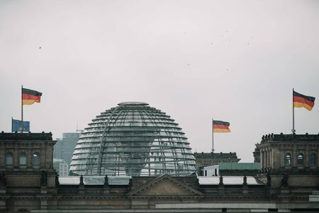 building of the German Bundestag with flags in bad weather