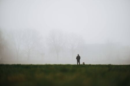man and his dog as symbol of loyal friendship waiting in fog