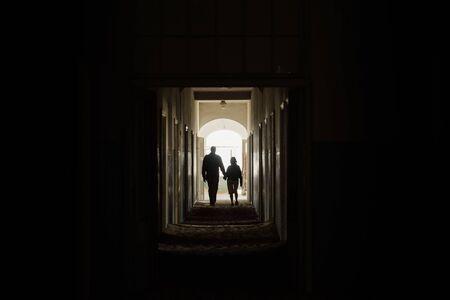 couple se tenant la main et marchant ensemble dans la lumière