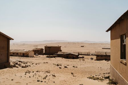 Abandoned buildings left to rot in wild west scenery with desert sand