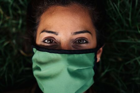 photo of a woman wearing a face mask lying in the grass
