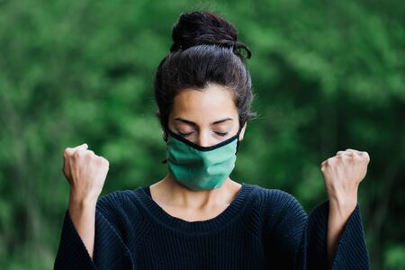 photo of a woman in the forest wearing a face mask and rasing her fists Stock Photo