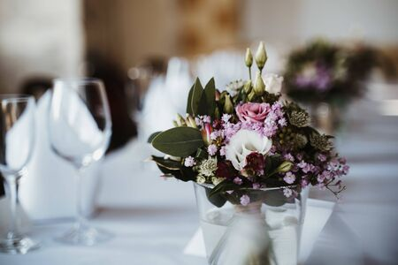 photo of flowers on a table in a vase with plates