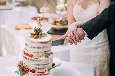 a bride and a groom cutting a strawberry wedding cake