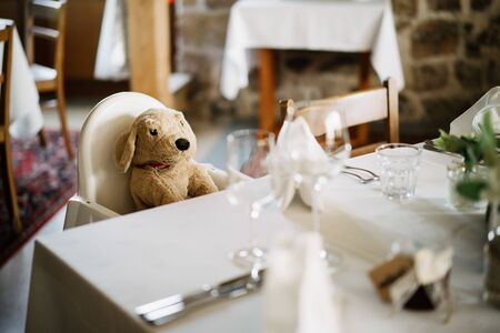 a teddy bear sitting at at a table chair