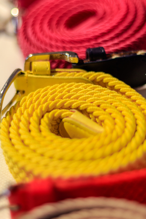 Great selection of colorful, yellow and magenta canvas belts rolled up in a fashion store.