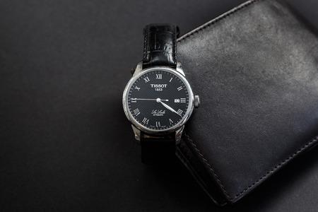 Budapest, Hongrie - 10 septembre 2017: Le Tissot Le Locle est une montre en cuir noir avec un portefeuille en cuir noir sur fond gris foncé. Banque d'images - 85744162