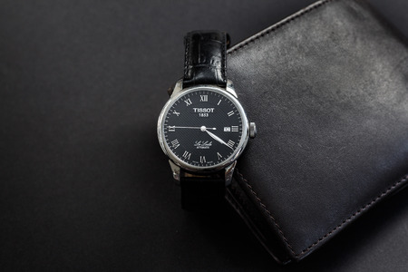 Budapest, Hungary - September 10, 2017: The Tissot Le Locle is a black leather watch with a black leather wallet on a dark gray background. Stock Photo - 85744162