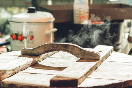 Rusty wooden lid on a boiling pan. Photo of an outdoor pop-up kitchen with a vintage ceramic pot in the background and a wooden cover on a pan, letting out a small amount of steam.