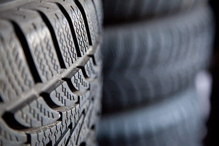 winter tires: winter tires in a stack. They are quite new. one stack is out of focus