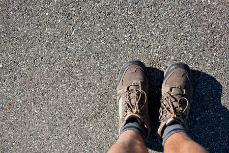 subjective: hiking boots on concrete ground from a subjective perspective. Stock Photo