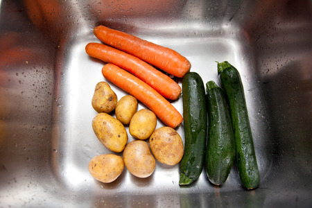 sinks: vegetables, carrots, potatoes and zucchini in the kitchen sink
